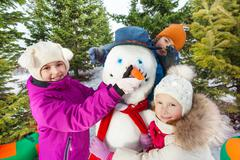 Close-up of happy children build cheerful snowman - stock photo
