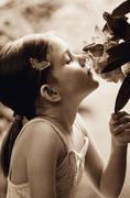 Ballerina sniffing a flower - stock photo