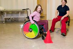 Girl learning to use wheelchair Stock Photos