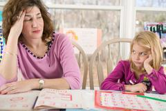 Frustrated mother helping bored daughter with homework Stock Photos