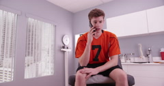 Caucasian college athlete talking on a cell phone inside a clinic Stock Footage