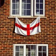 England flag hanging from a window Stock Photos