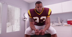 College football player waiting in doctor's office for bad news Stock Footage