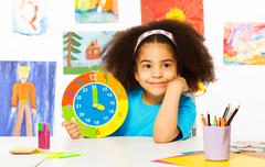 Small African girl holding showing time - stock photo