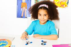 Cute African girl learn numbers with coins - stock photo