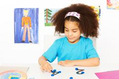 Girl puts blue coins learning to count - stock photo
