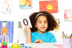 African girl holds flashcard with zero at  desk Stock Photos
