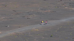 Tourist walking in the volcano crater - Hawaii, zoom out shot Stock Footage