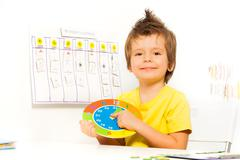 Smiling boy holding colorful carton clock sitting Stock Photos