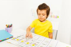 Boy plays in developing game pointing at calendar Stock Photos