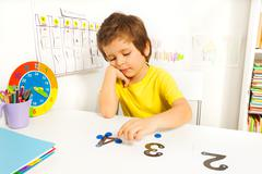 Boy puts learn to count with numbers and values Stock Photos