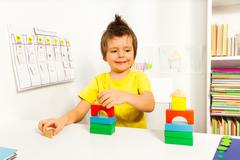 Smiling boy replicating example with color blocks - stock photo