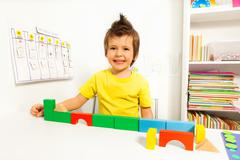 Laughing cute boy putting blocks in sequence Stock Photos