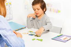 Preschooler boy and developing game with card - stock photo