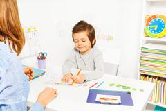 Boy colors shapes during ABA with therapist near Stock Photos