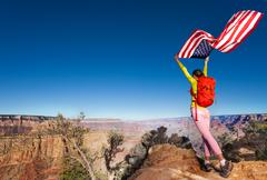 Woman and US flag on Independence Day Grand Canyon - stock photo