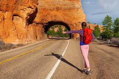 Hitch-hiking girl with rucksack near Red canyon - stock photo