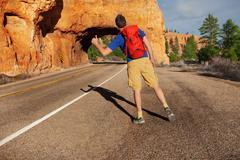 Hitch-hiking man with rucksack near Red canyon Stock Photos