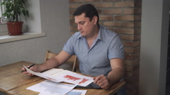 Manager analyzes the sales charts while sitting in the office Stock Footage