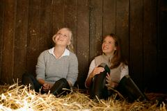 Two young women in a stable - stock photo