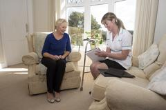 Nurse on a home visit talking with an elderly female patient - stock photo
