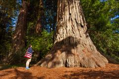 Man with US flag on shoulders stands near big tree - stock photo