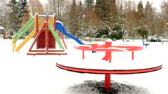Winter playground with seesaw, slider, ladder, turning merry-go-round. Stock Footage