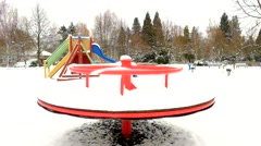 Winter playground with seesaw, slider, ladder, turning merry-go-round. - stock footage