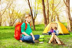 Happy boy with red backpack resting at camp - stock photo