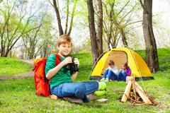 Happy boy with red backpack and binocular at camp - stock photo