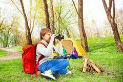 Boy wearing red backpack watches through binocular - stock photo