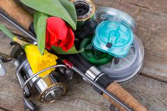 fishing tackles with spring flowers - stock photo