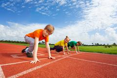 Two boys and girl on bended knee ready to run - stock photo