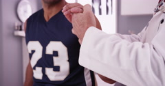 College basketball player with sports injury being examined by doctor Stock Footage