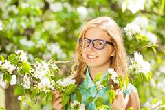 Teenager girl wearing glasses near white flowers - stock photo