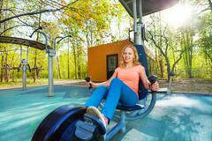 Blond teenage girl cycling on exercise equipment Stock Photos