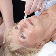 Stock Photo of Nurse administering nasal drops into a patients nose