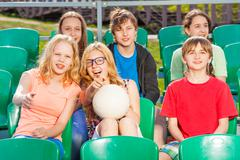 Happy teenagers sitting on the tribune during game - stock photo