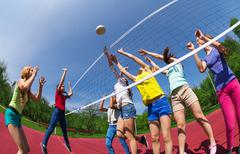 Active teenagers playing volleyball on game court Stock Photos