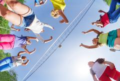 View from below of kids playing volleyball Stock Photos
