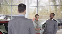 4K Portrait of smiling salesman talking to customers in car dealership.  Arkistovideo