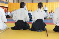 People in kimono and hakama sitting on tatami on martial arts training Stock Photos