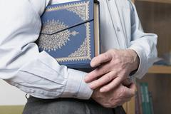 Hands holding the Koran - stock photo