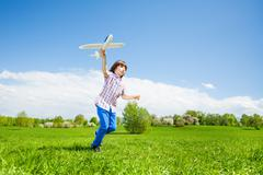 Active boy holding airplane toy during running Stock Photos
