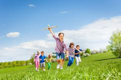 Happy cute boy with plane toy and chasing him kids Stock Photos