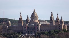 Imposing Palau Nacional telephoto view at sunny day, airliner fly on back Stock Footage