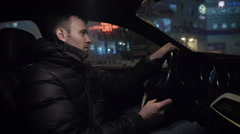 Driving a car at night -man driving his modern car at night in a city - stock footage