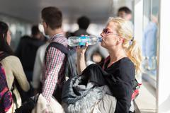 Woman drinking water while queuing to board plane. Stock Photos