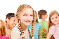 School girl with ponytails and group of friends - stock photo