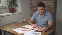 The manager checks the sales data for the month, are on the table the documents Stock Footage